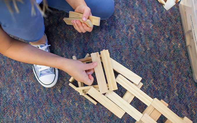 Child Building with Wooden Blocks